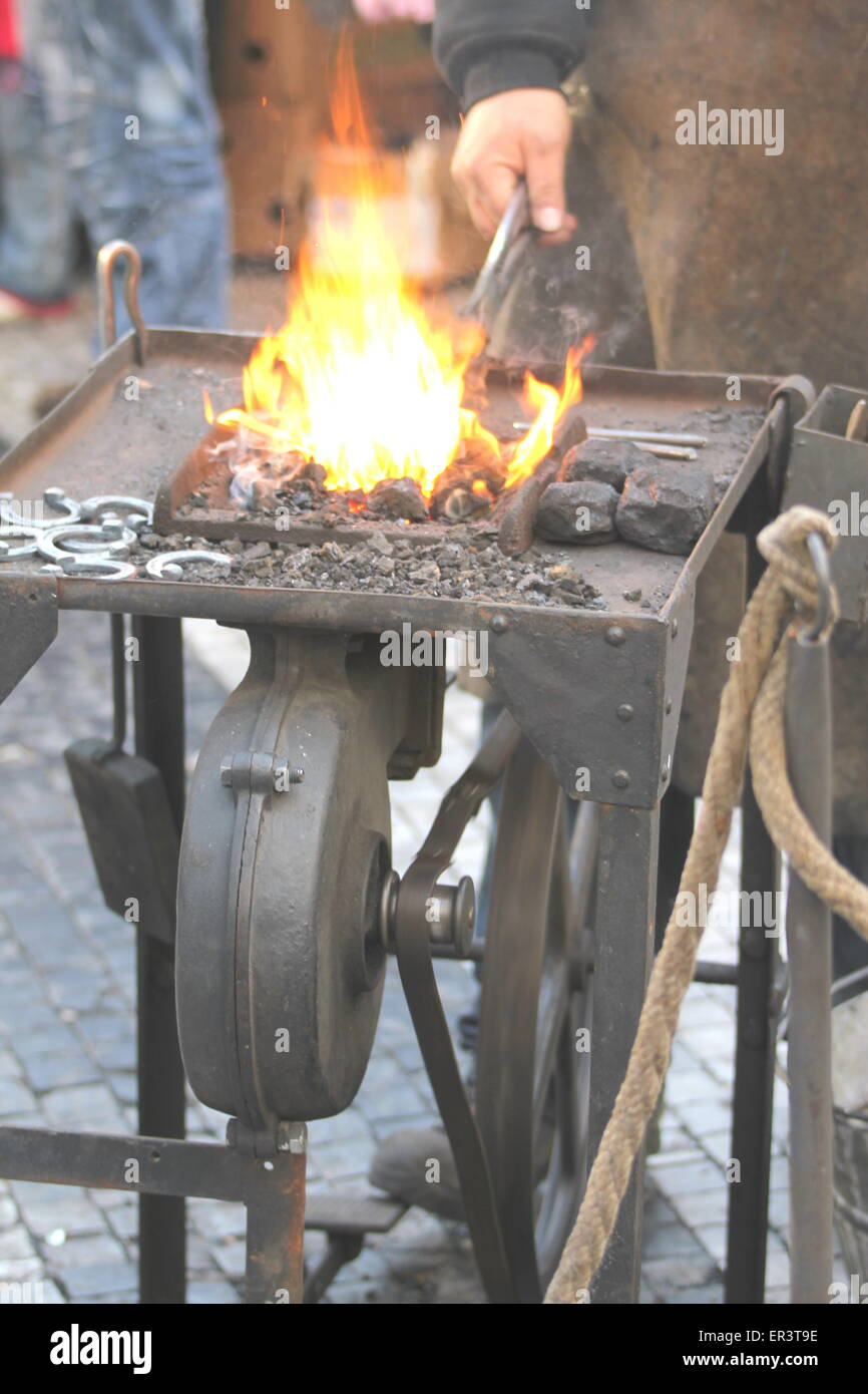 Craftsman working with fire beating iron. - Stock Image