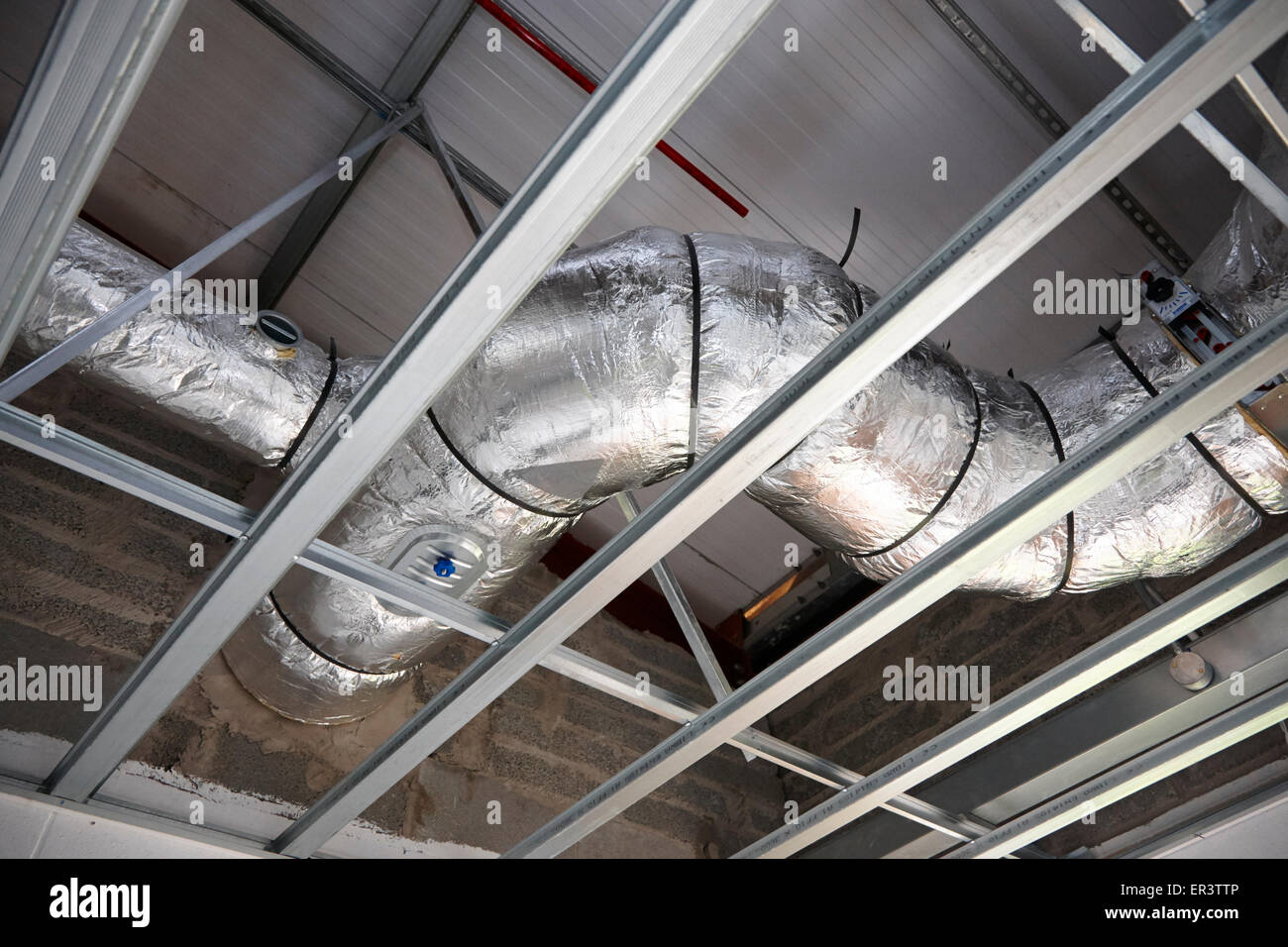 overhead air extraction conditioning conduit pipes in an industrial building under construction in the uk - Stock Image