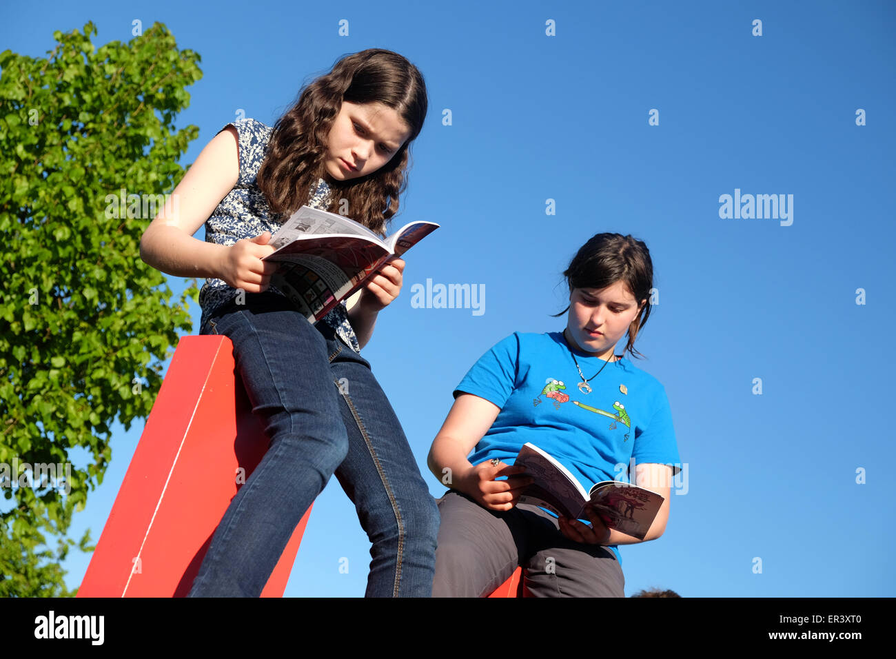 Hay Festival, Powys, Wales - May 2015  -  Two young girls reading books on top of the giant HAY sign on the Festival Stock Photo
