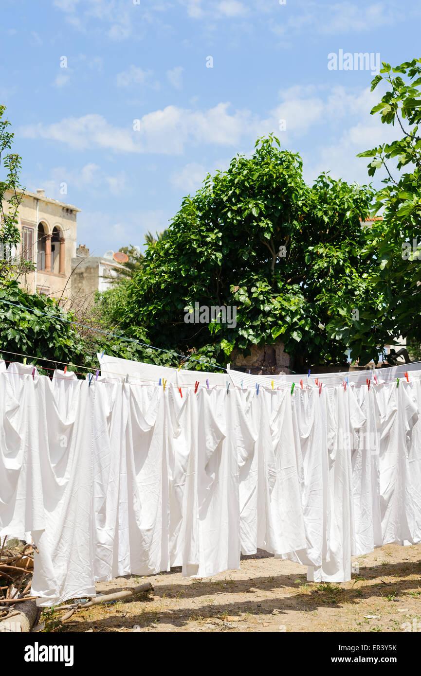 Linen sheets drying on a rope in Cunda Alibey Island Ayvalik, Balikesir Turkey - Stock Image
