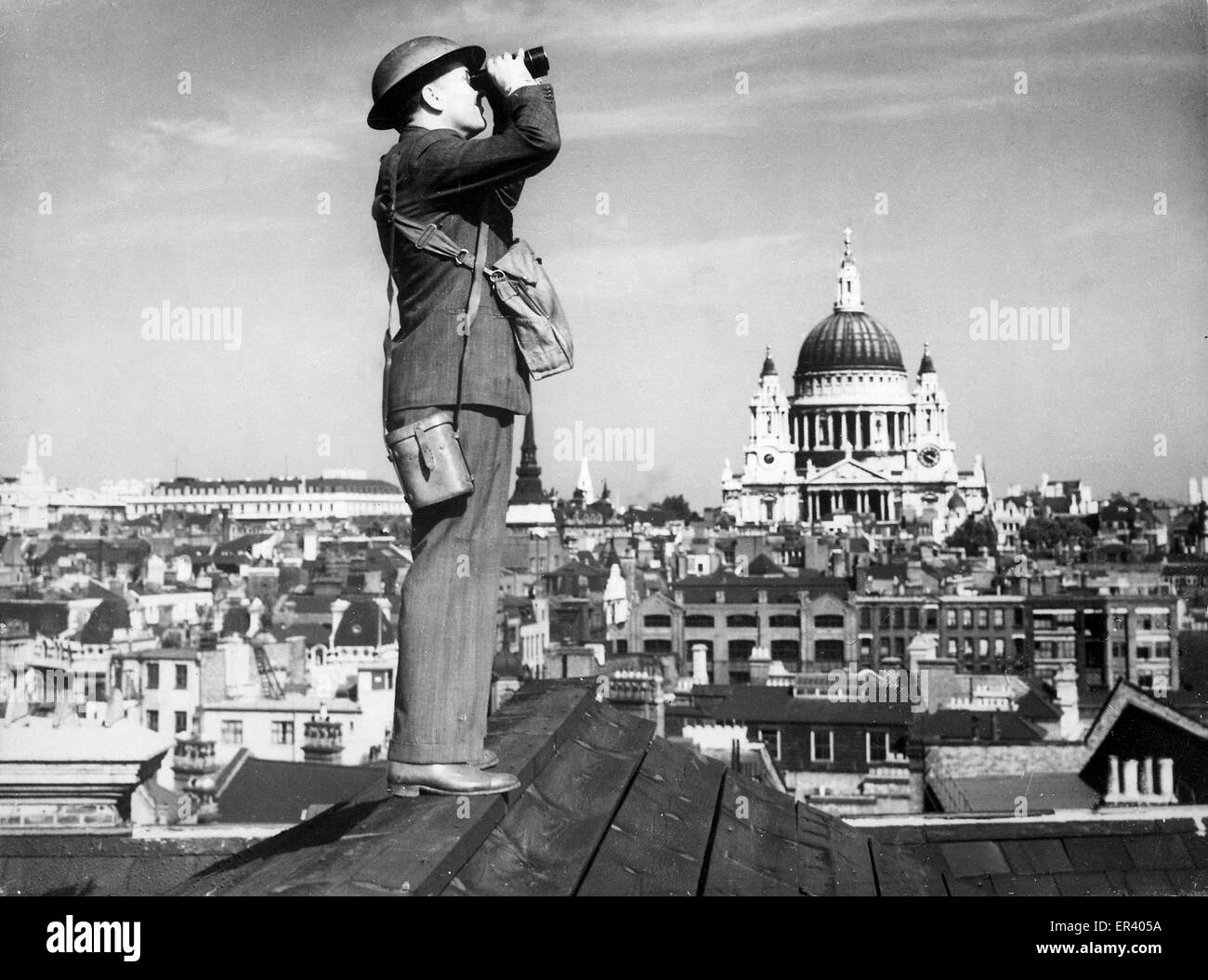 A Royal Observer Corps spotter scans the skies of London. Battle of Britain air observer keeping watch over London - Stock Image