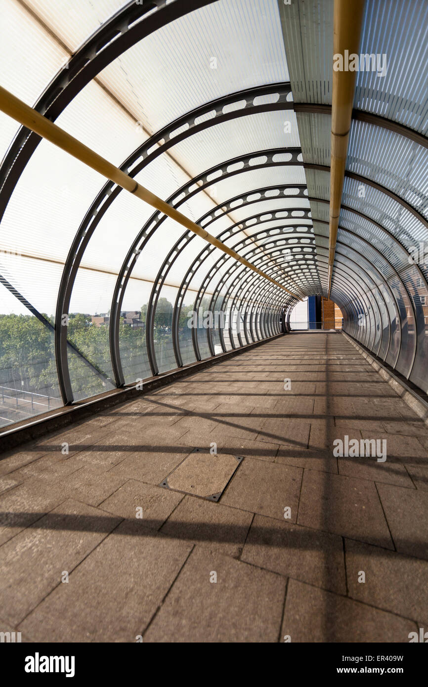 Poplar DLR station high-level walkway, a cable stayed footbridge with curved glass canopy in the London docklands, - Stock Image