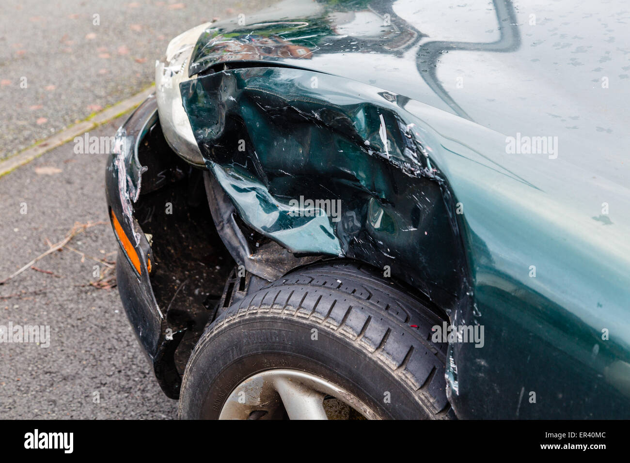 Car with damage to front wing on drive - Stock Image