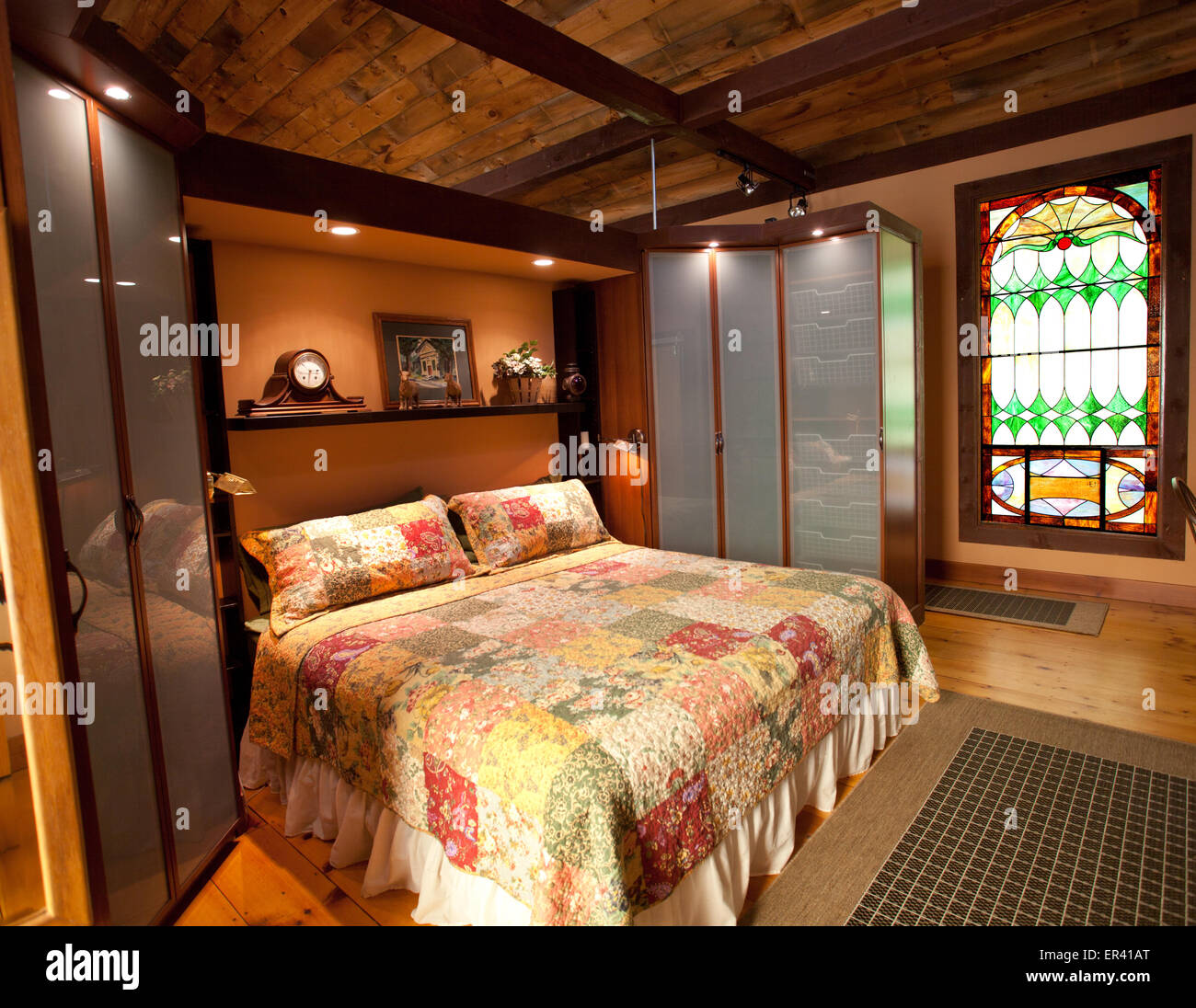 Interior detail of master bedroom. Vermont dairy barn renovated into a unique home featuring antique stained glass Stock Photo