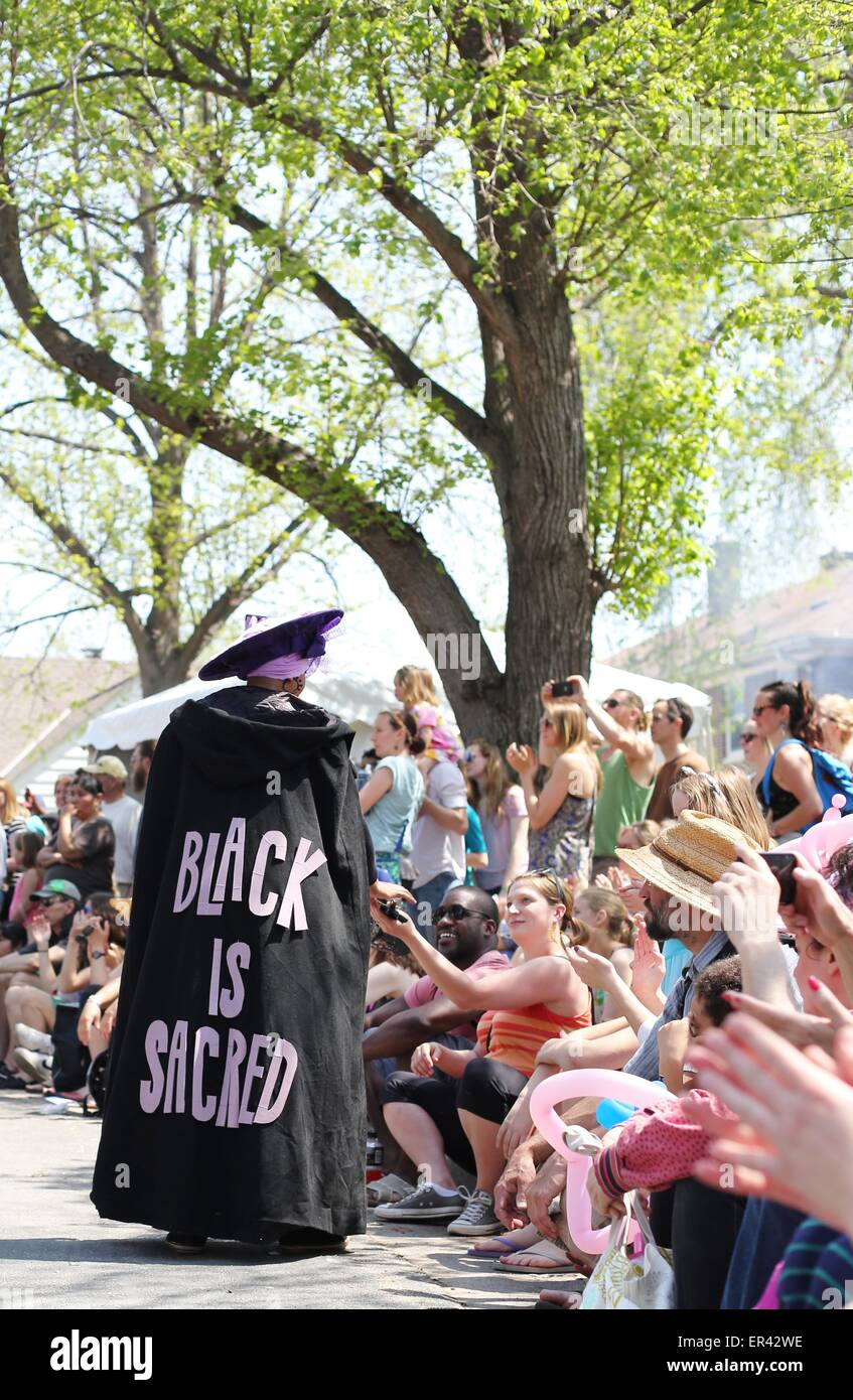 """A woman wearing a cape that reads """"black is sacred"""" at the May Day parade in Minneapolis. Stock Photo"""