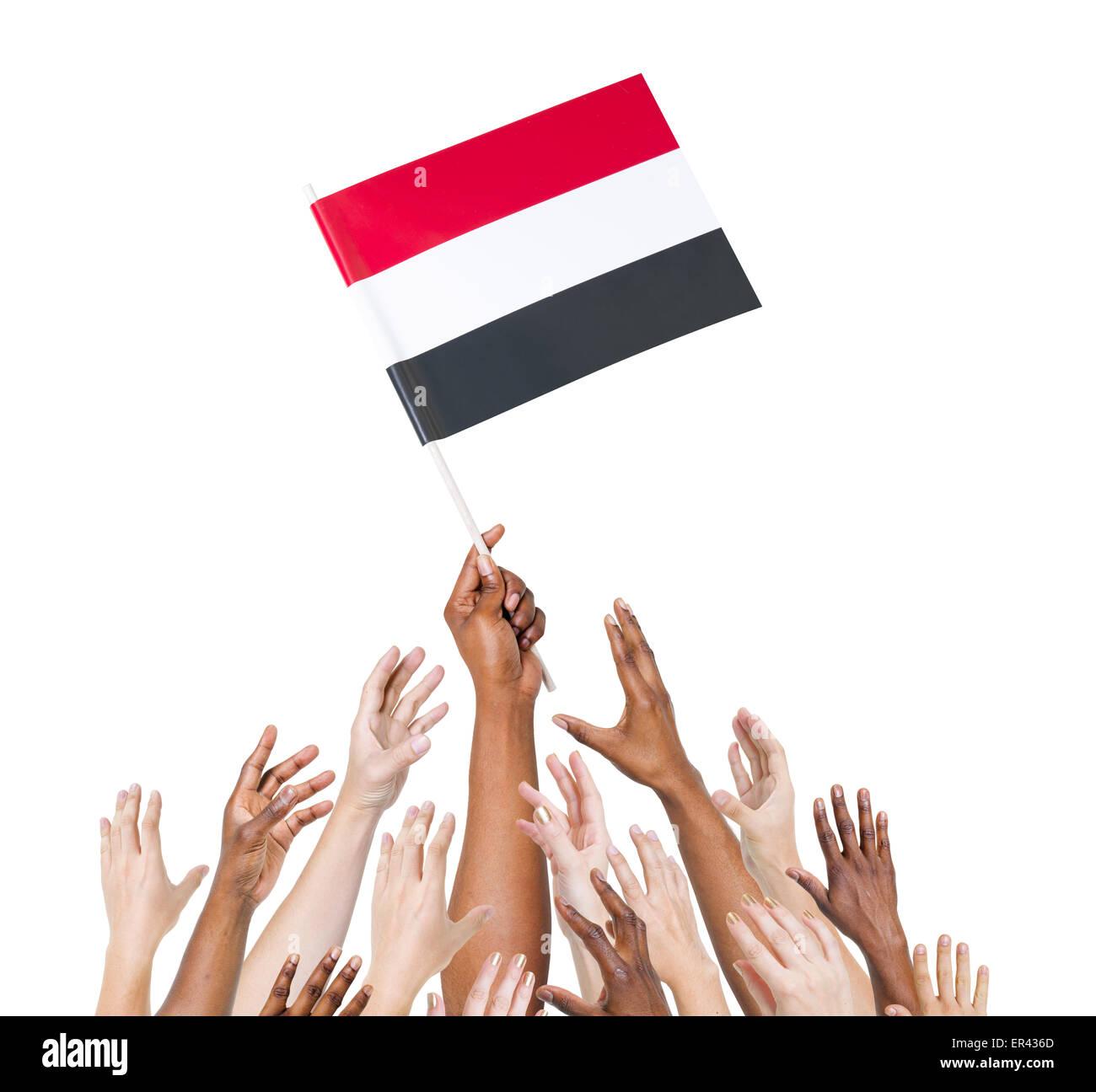 Human hand holding Yemen flag among multi-ethnic group of people's hand Stock Photo