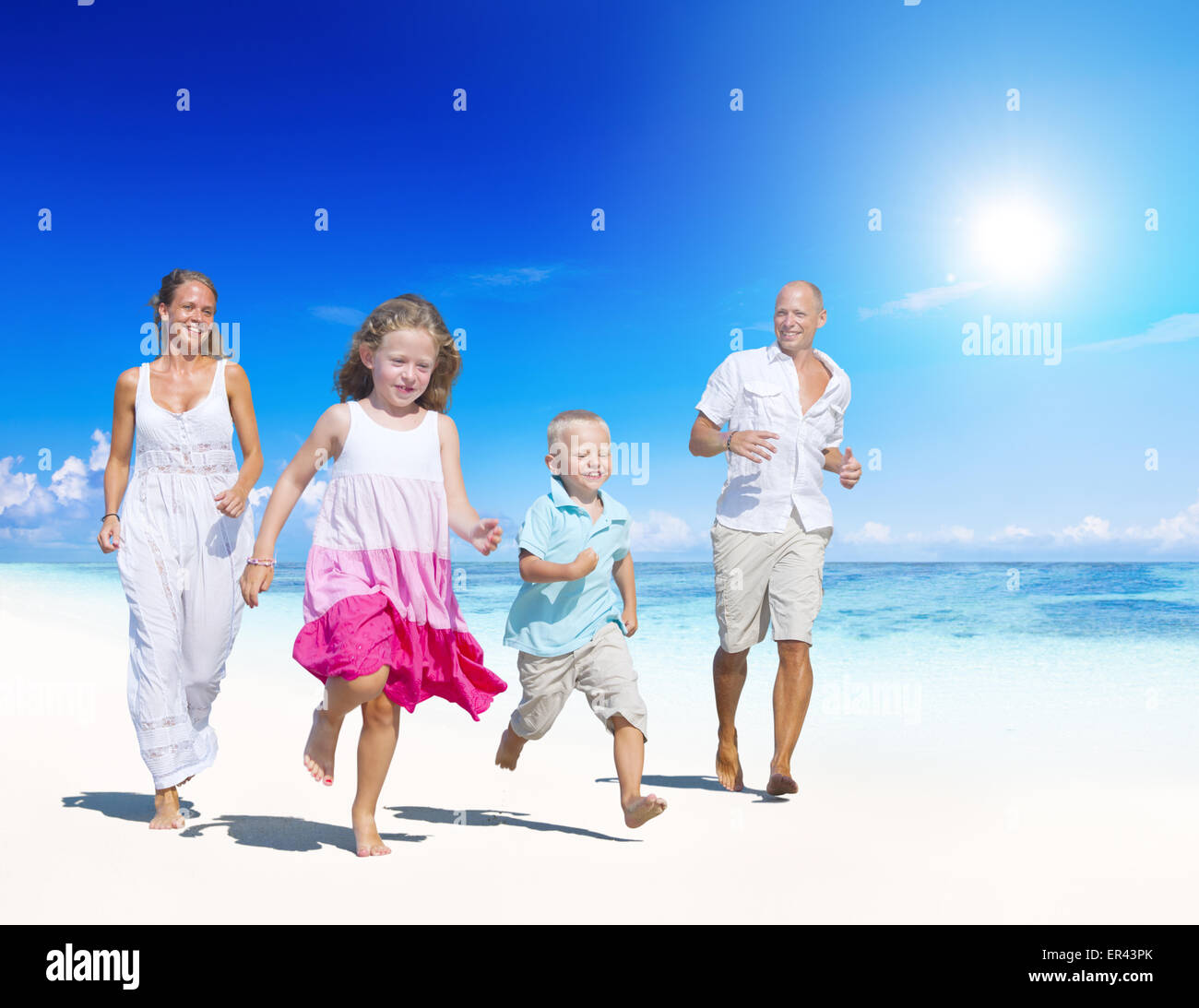 Family having fun on a beach.  Young family enjoying their summer vacation. - Stock Image