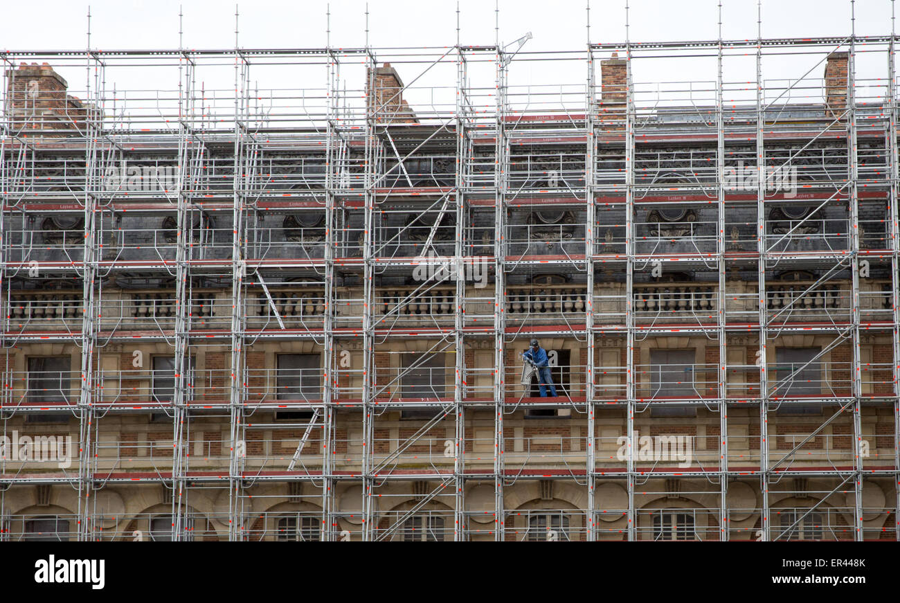 A worker with restoration and preservation scaffolding setting up on the exterior of the Château de Versailles, - Stock Image