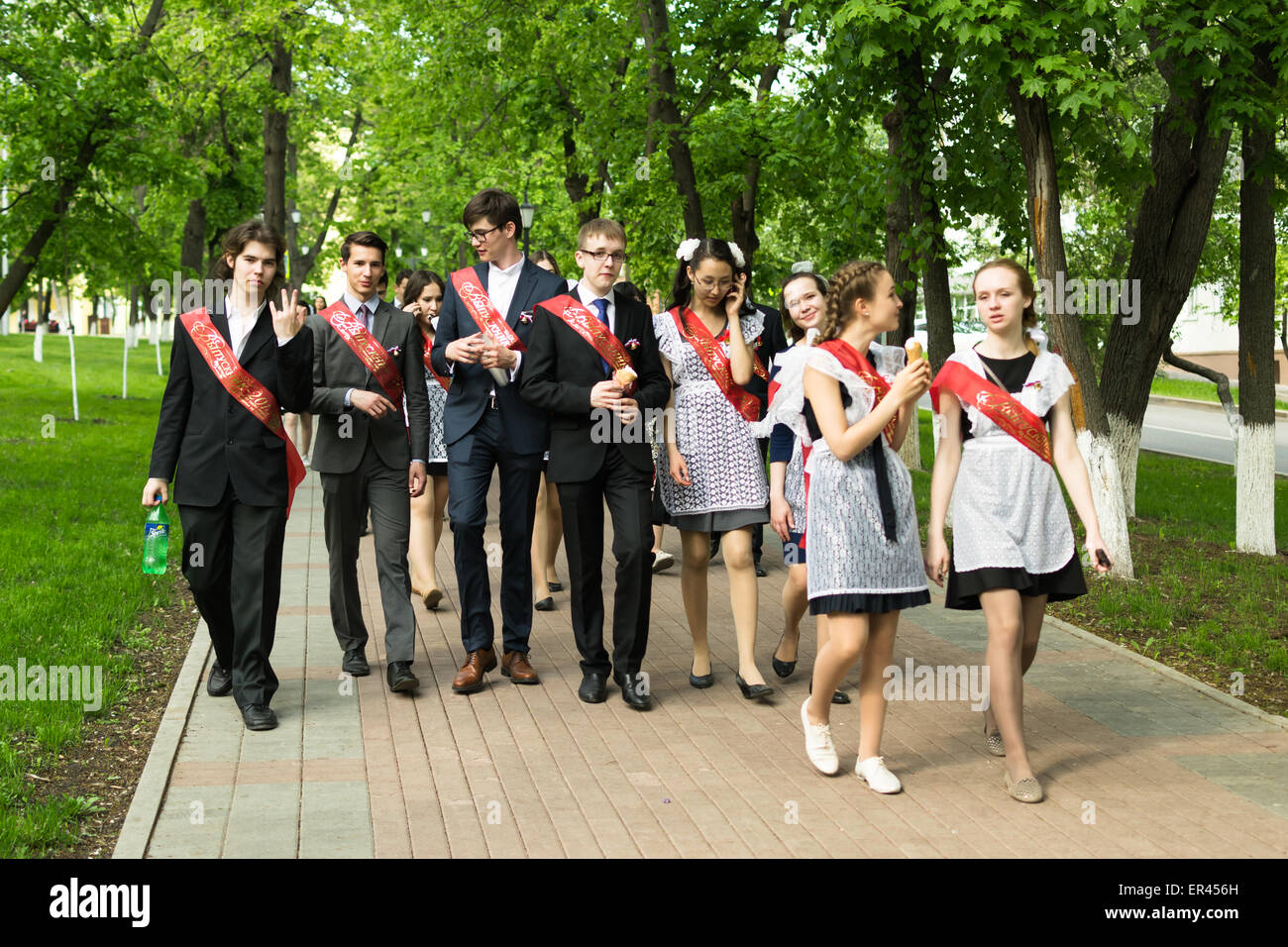 Group of Russian schoolchildren in traditional uniform celebrating graduation from high school in May 2015 - Stock Image