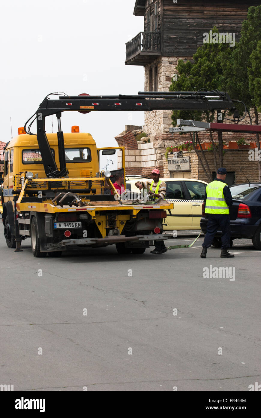 Employees of municipal cars evacuation service embarks a vehicle on a special truck - Stock Image