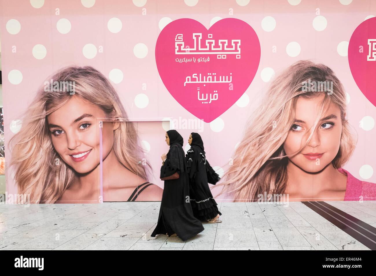 Women walk past billboard for new Victoria's Secret shop in City Centre shopping mall in Manama Kingdom of Bahrain - Stock Image