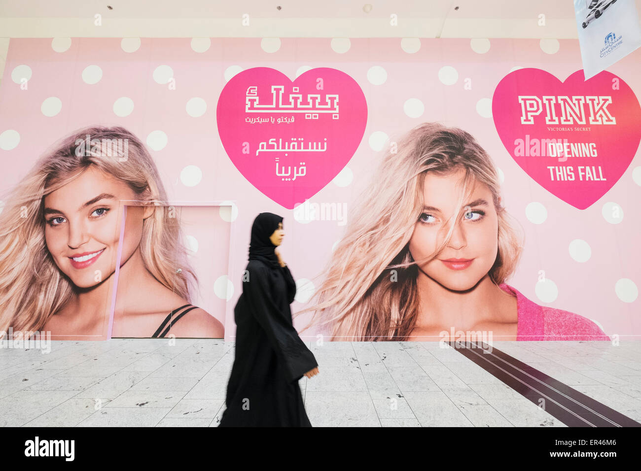 Woman walking past billboard for new Victoria's Secret shop in  City Centre shopping mall in Manama Kingdom - Stock Image