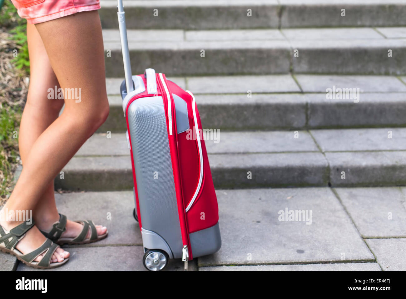 Feet of a young girl near red travel suitcase. - Stock Image