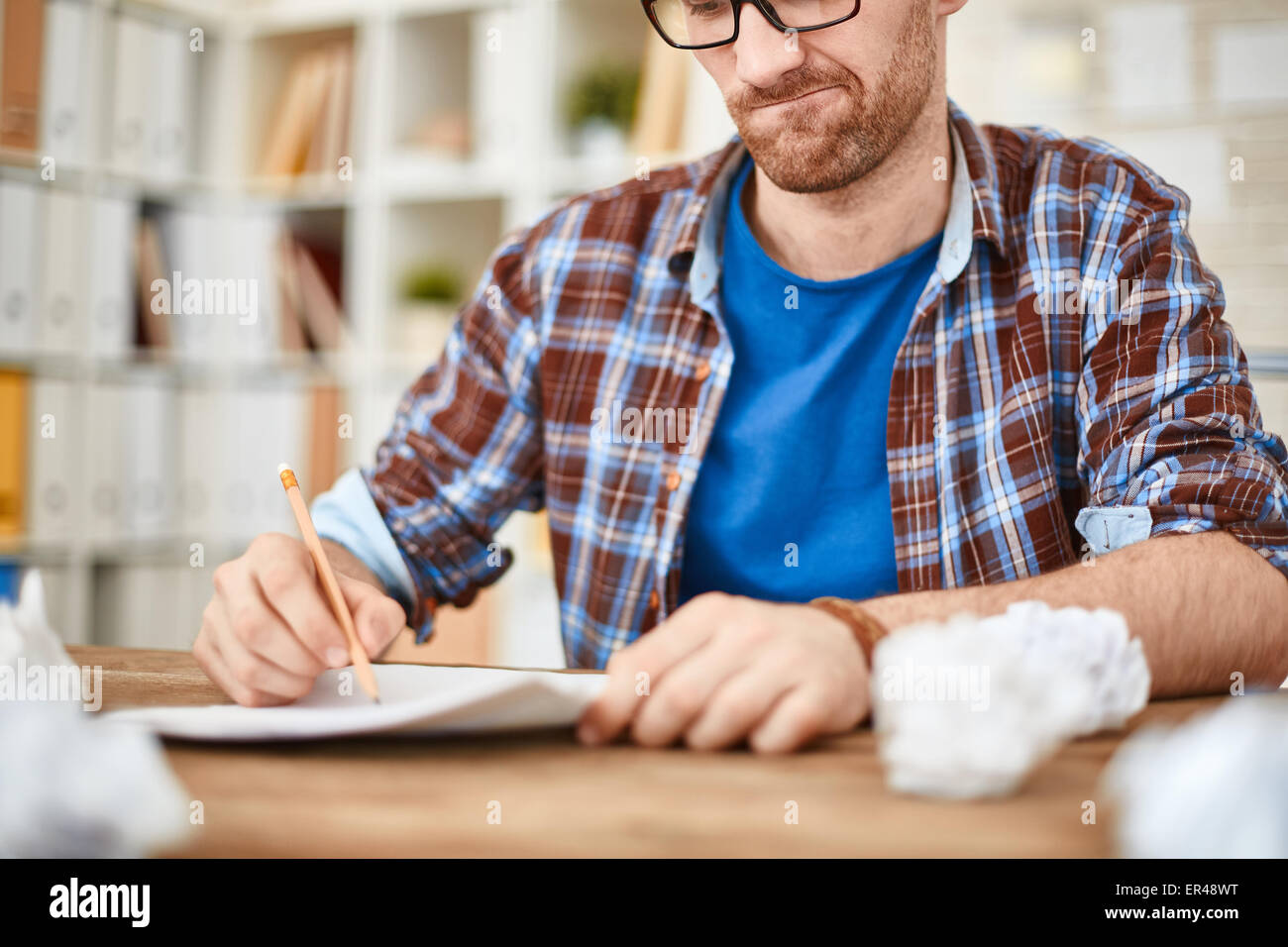 Young businessman with pencil writing down his ideas with crumpled sheets near by - Stock Image