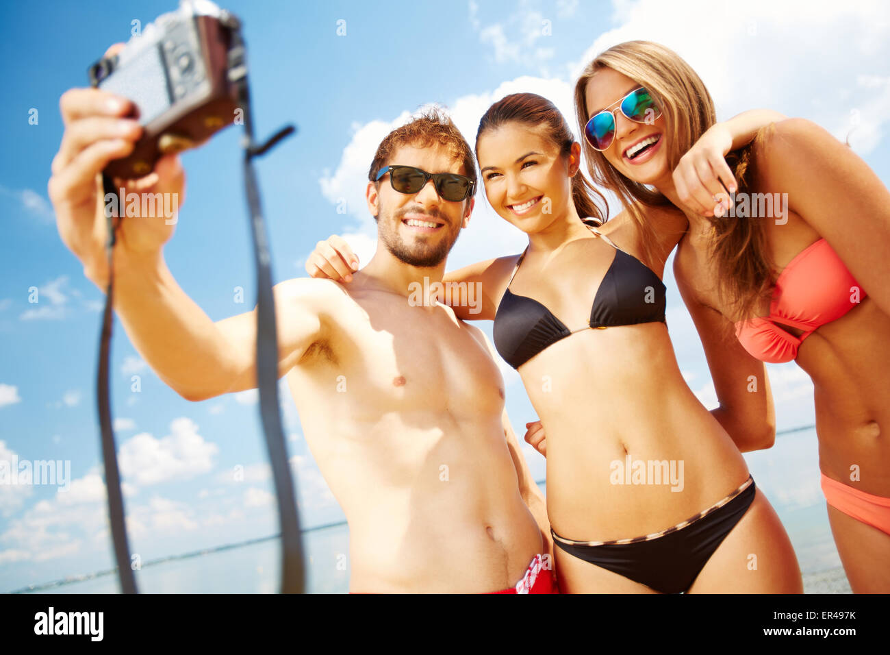 Happy friends taking photos on the beach - Stock Image