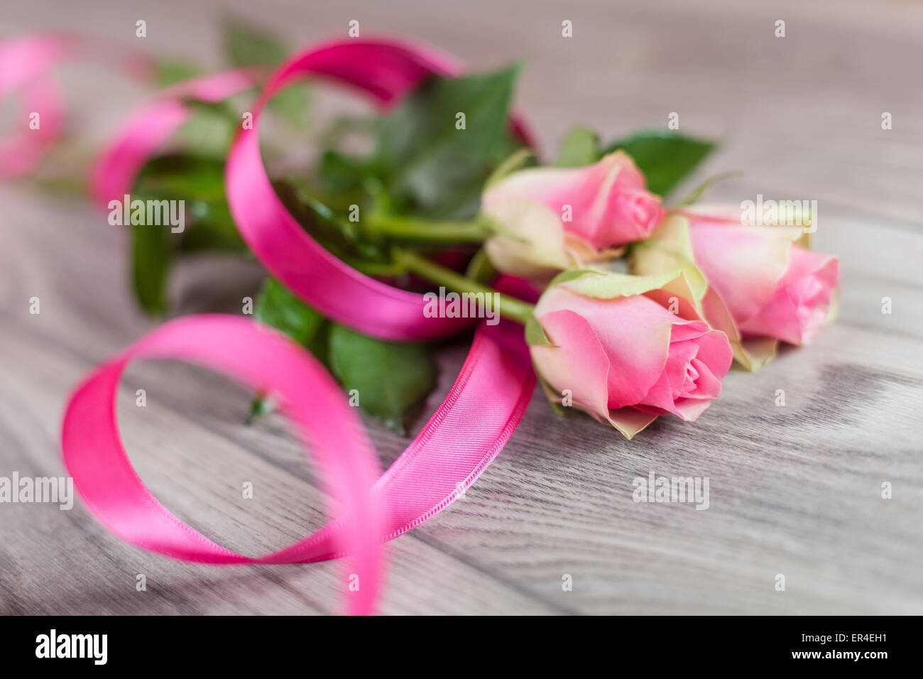 Tulips with a pink ribbon on a wooden table - Stock Image