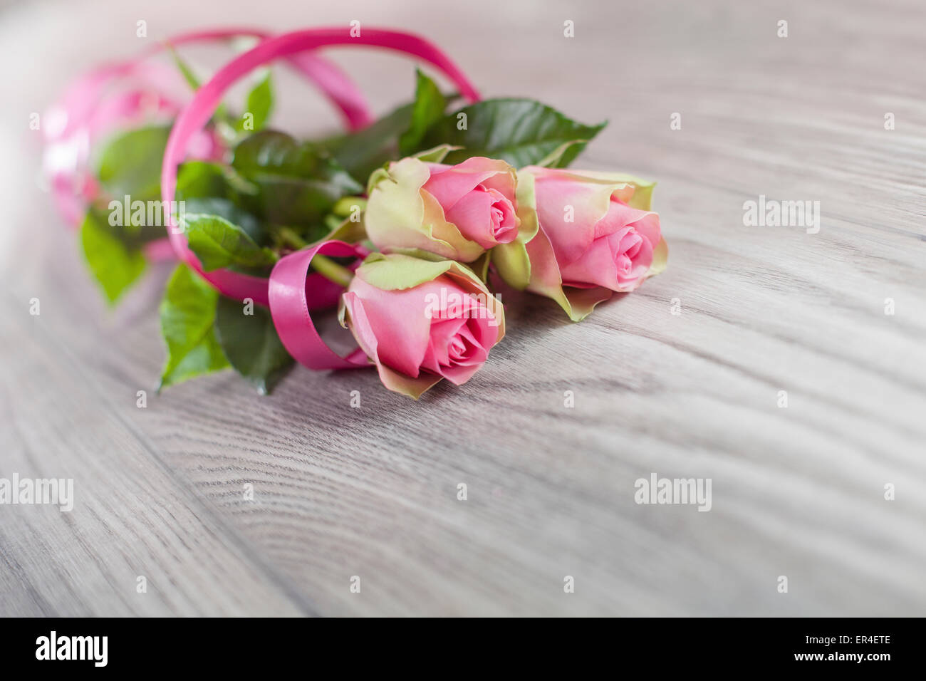 Pink roses on a wooden table - Stock Image