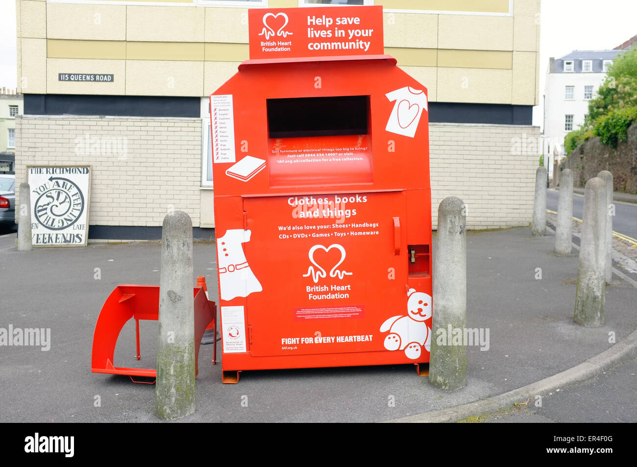 A red British Heart Foundation donations bin on the streets of Bristol. - Stock Image