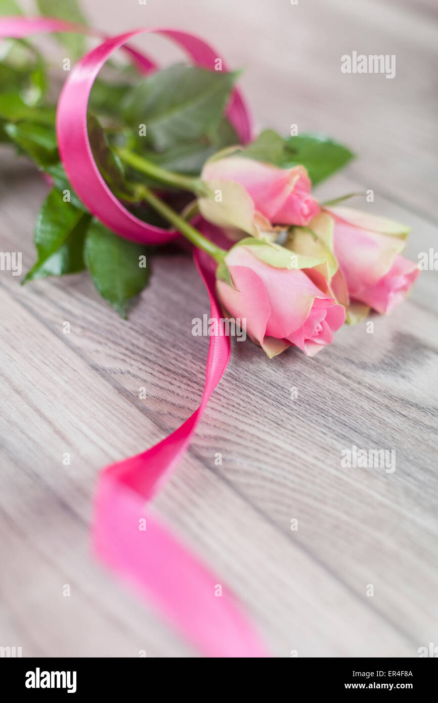 Pink roses on a wooden table Stock Photo