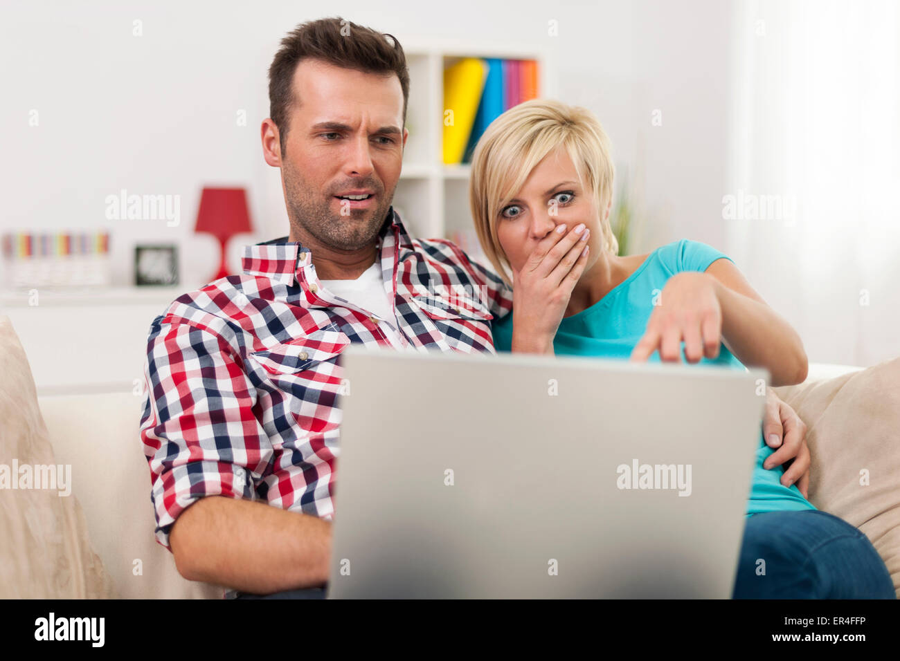 Young couple watching something on their laptop - Stock Image