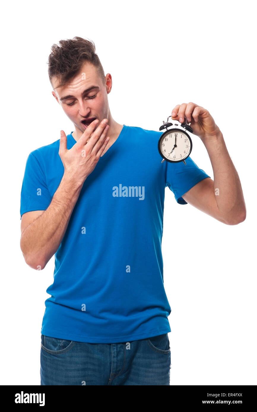 Young man posing with an alarm clock - Stock Image