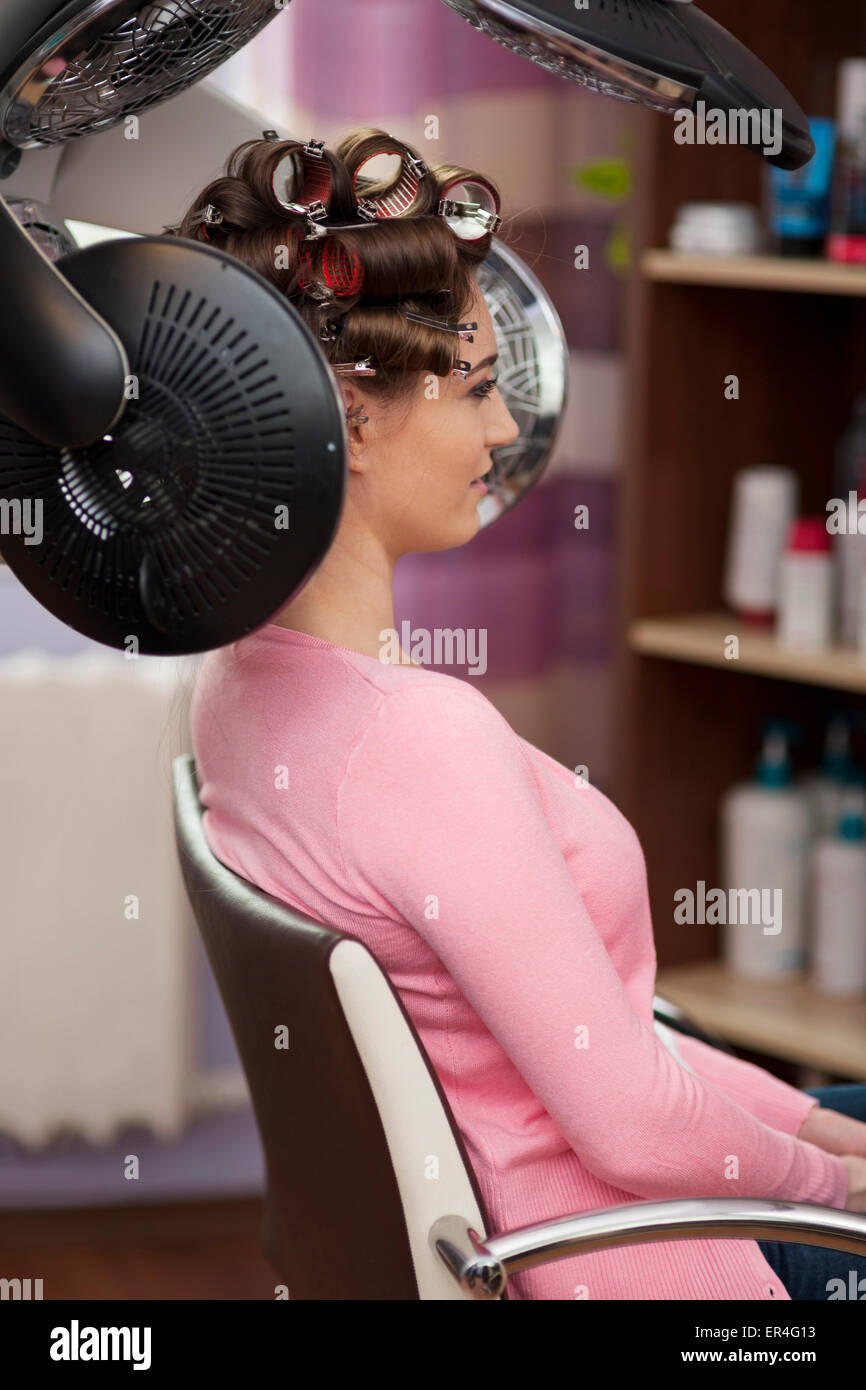 Young woman sitting under hair dryer with rollers. Debica, Poland - Stock Image