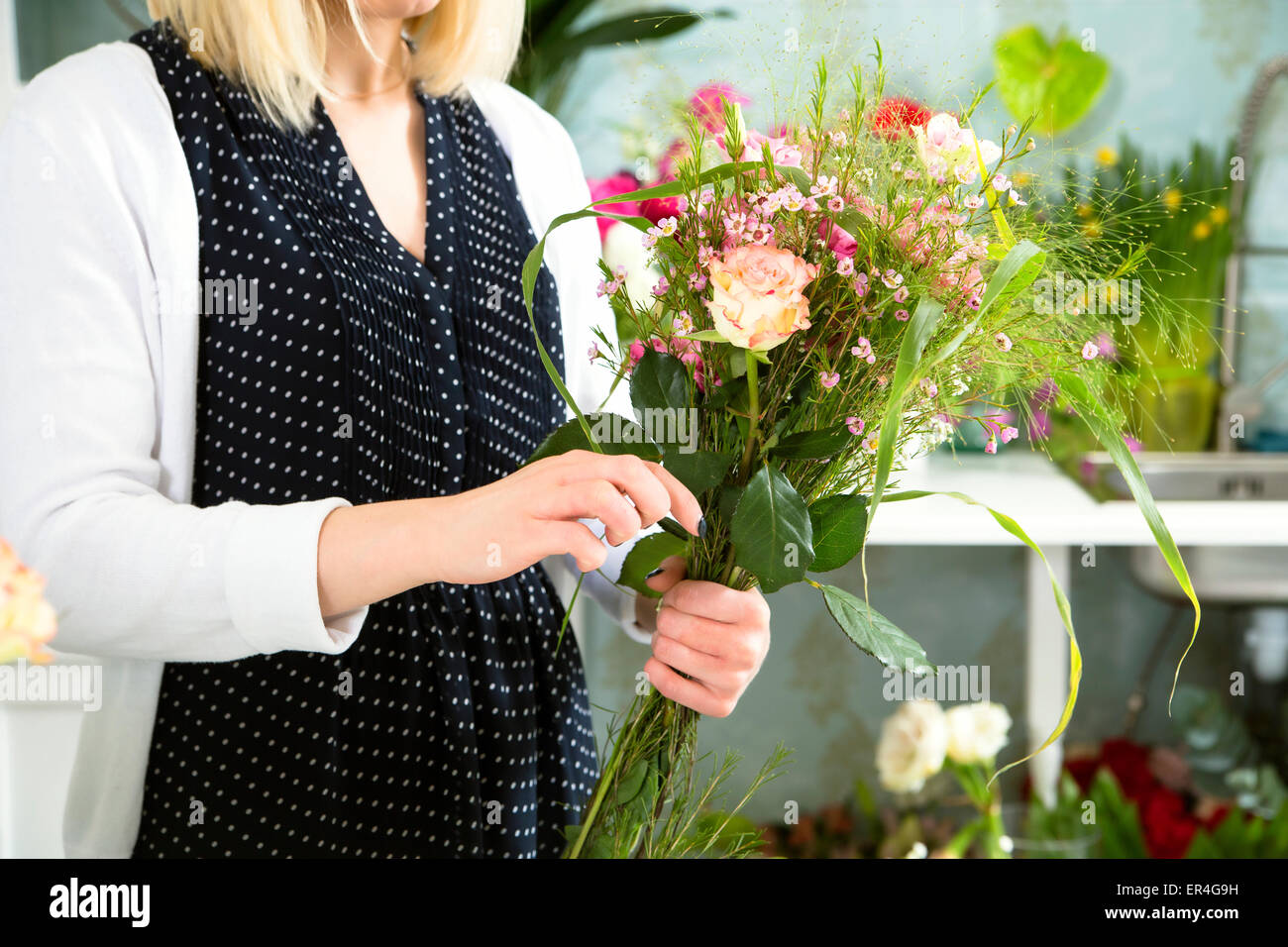 A young woman finishing beloved floral composition - Stock Image
