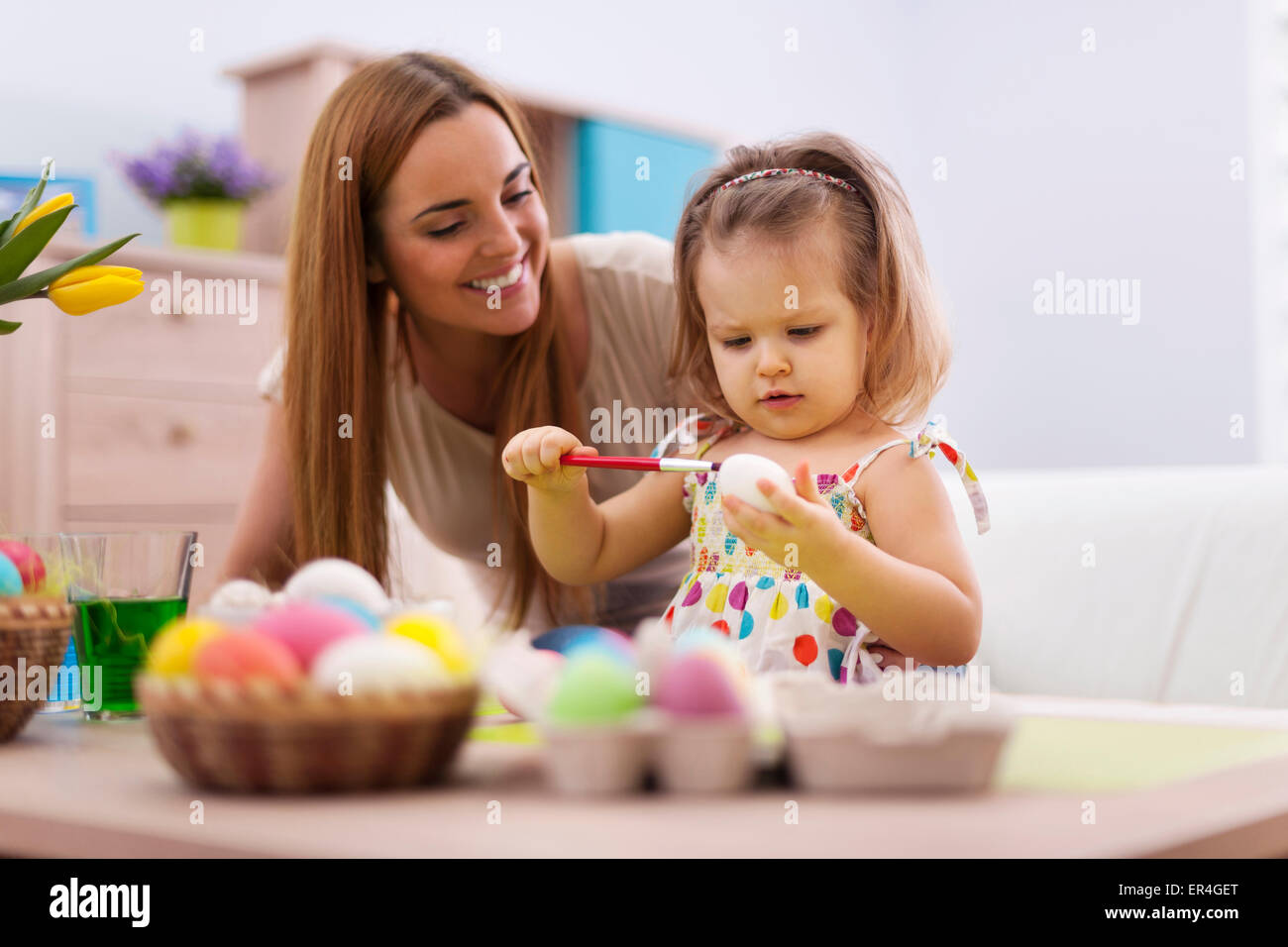 Family playing during painting easter eggs. Debica, Poland - Stock Image