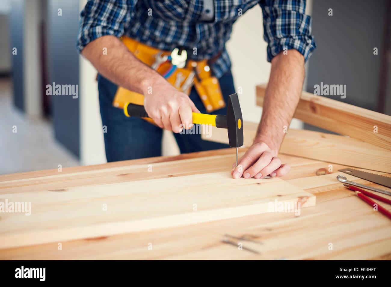 Close up of man hitting nail by hammer. Pilzno, Poland - Stock Image