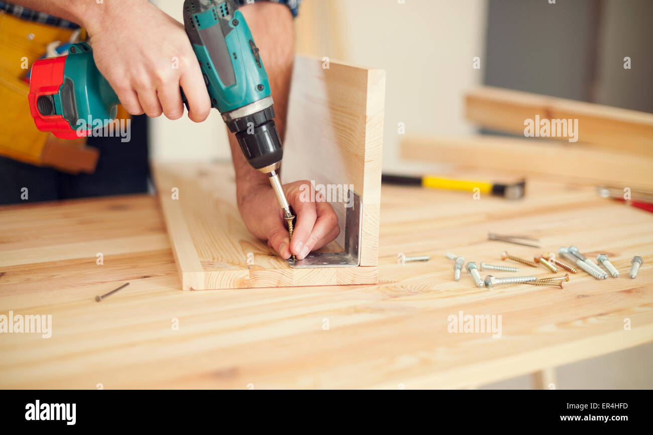 Close up of carpenter working with drill. Pilzno, Poland - Stock Image