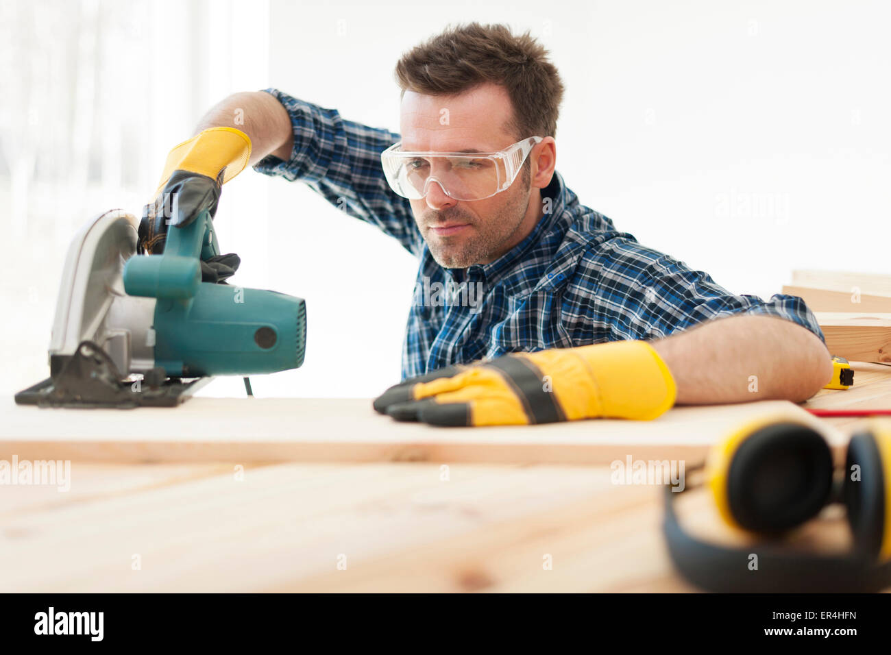 Focus carpenter cutting wooden plank. Pilzno, Poland - Stock Image
