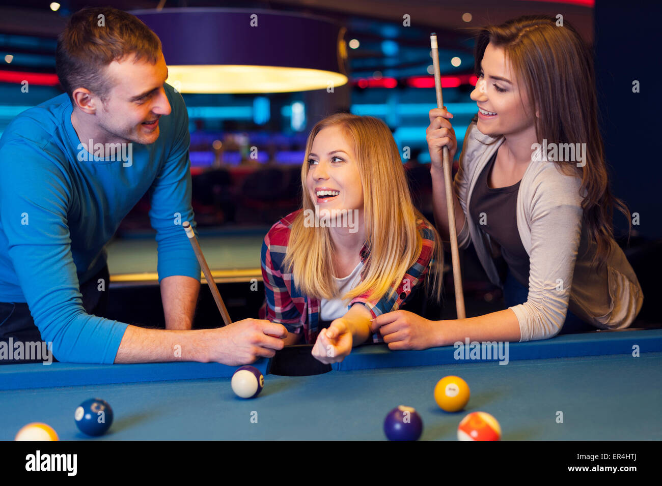 Friends hanging out at the pool table - Stock Image
