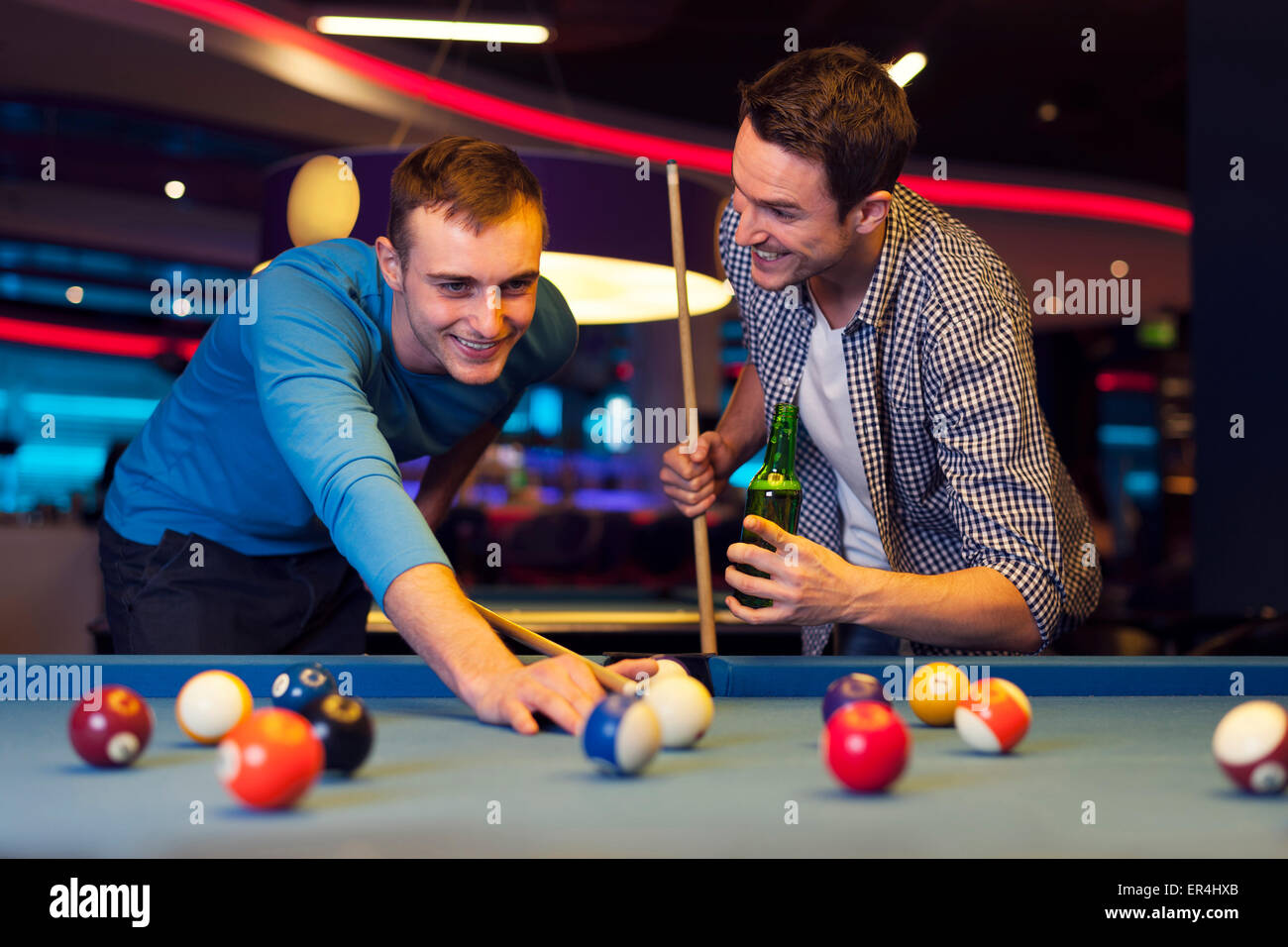 Friends playing pool at a bar - Stock Image
