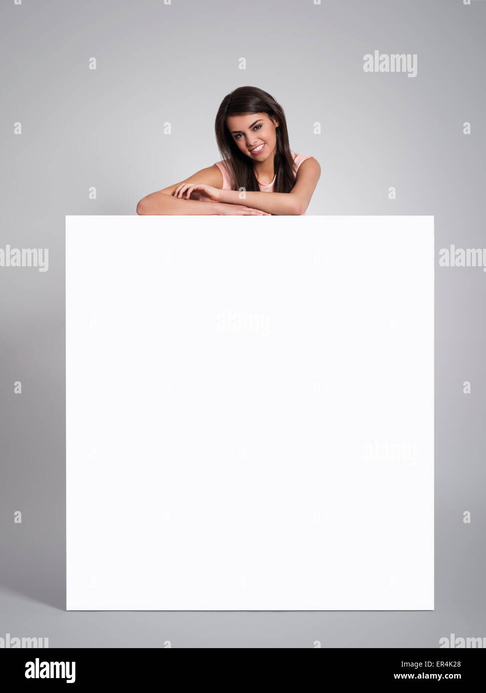 Smiling beautiful woman leaning on empty whiteboard. Debica, Poland - Stock Image