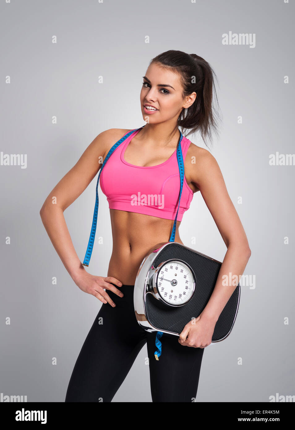 Happy woman holding weight scale. Debica, Poland - Stock Image
