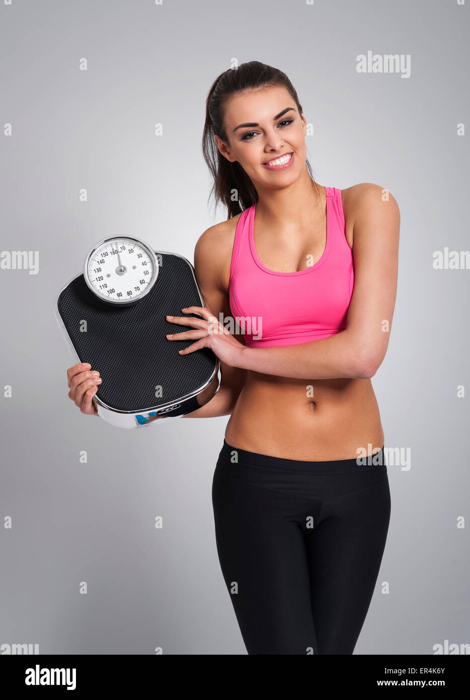 Smiling woman controlling her weight. Debica, Poland - Stock Image
