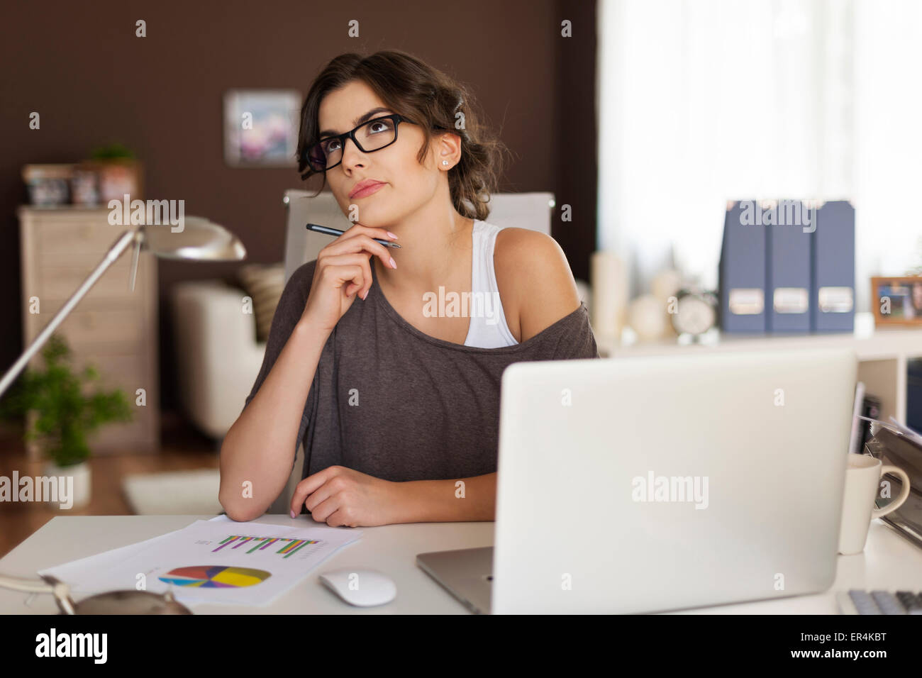 Thoughtful woman working at home. Debica, Poland - Stock Image