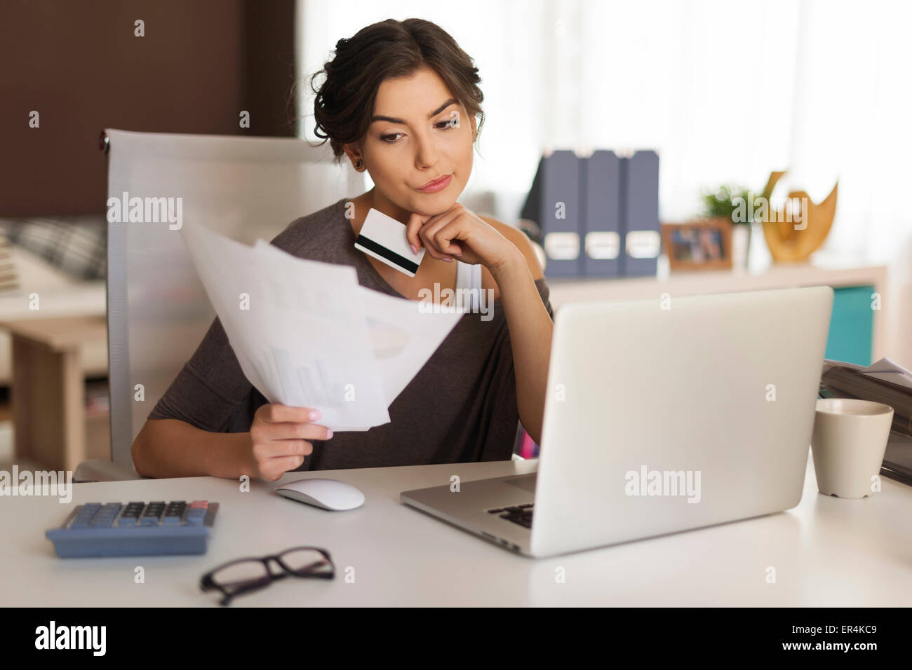 Pensive woman paying bills at home. Debica, Poland - Stock Image