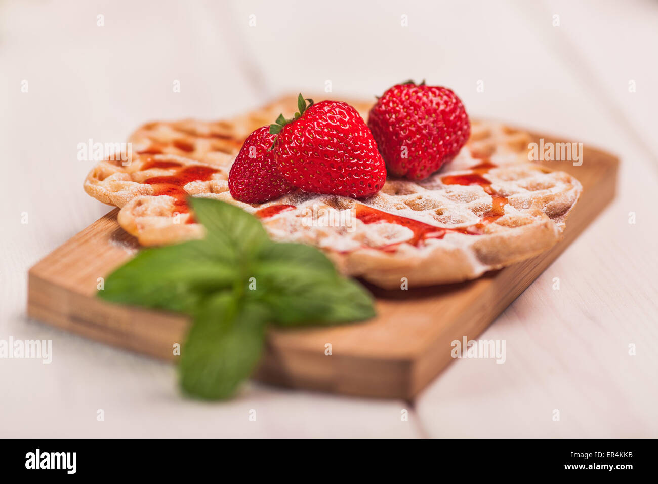 Waffles with strawberry on wooden plank. Debica, Poland - Stock Image