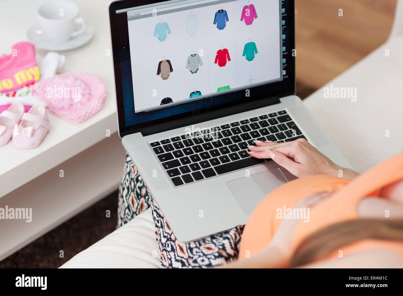 Pregnant woman buying clothes for baby at home. Debica, Poland Stock Photo