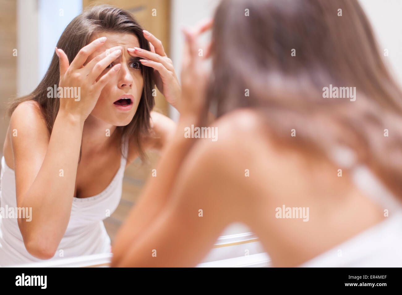 Shocked woman squeezing pimple in bathroom. Debica, Poland - Stock Image
