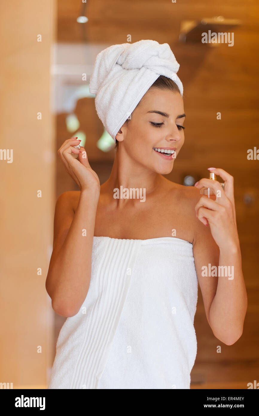 Beauty woman wrapped in towel applying perfume. Debica, Poland - Stock Image
