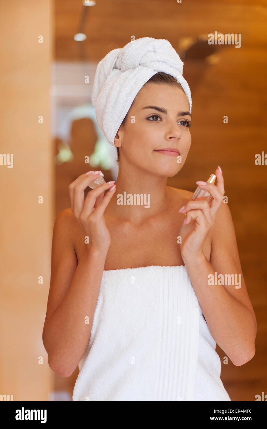 Attractive woman spraying herself perfume after shower. Debica, Poland - Stock Image