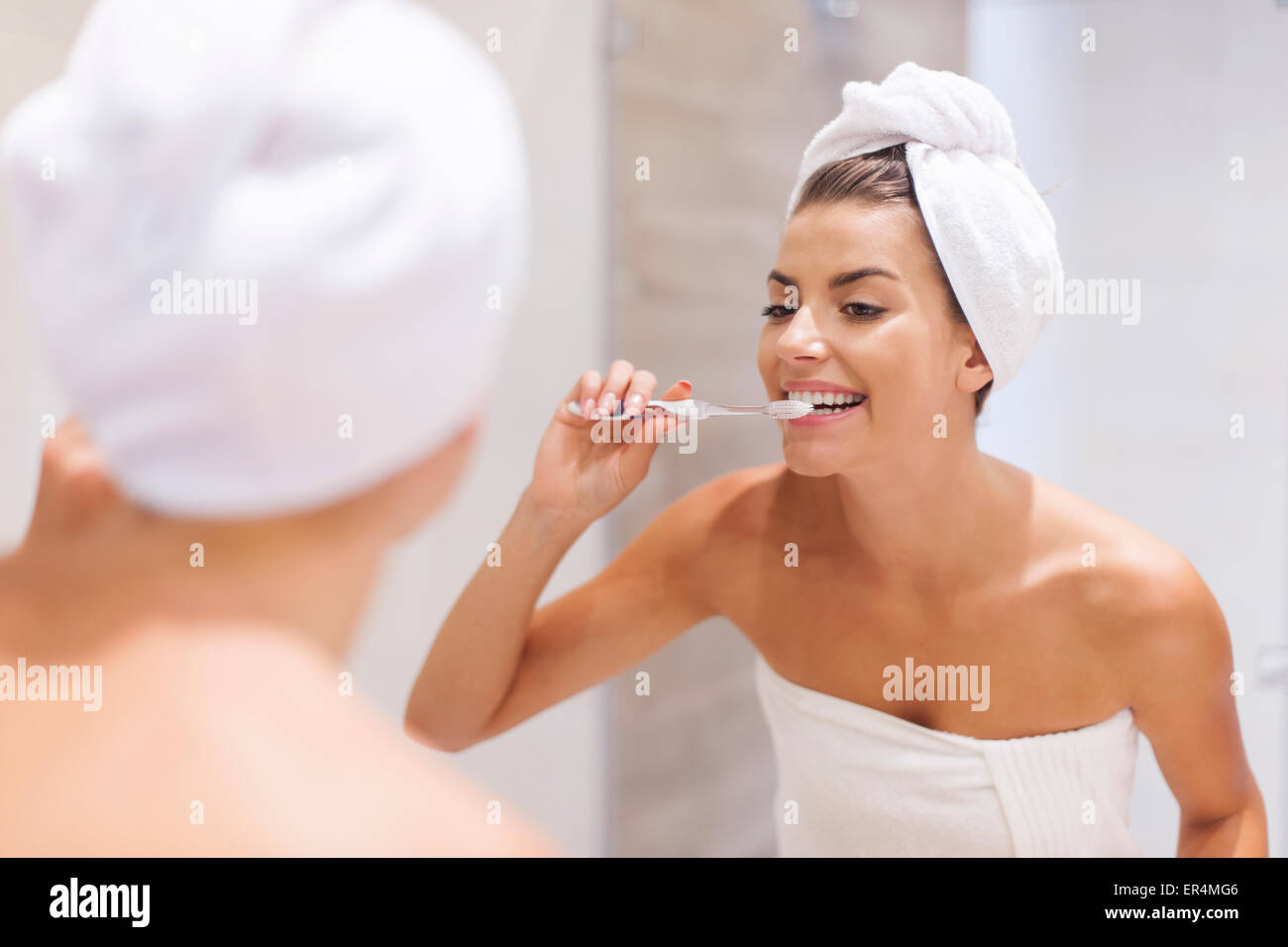 Young woman brushing teeth in bathroom. Debica, Poland - Stock Image