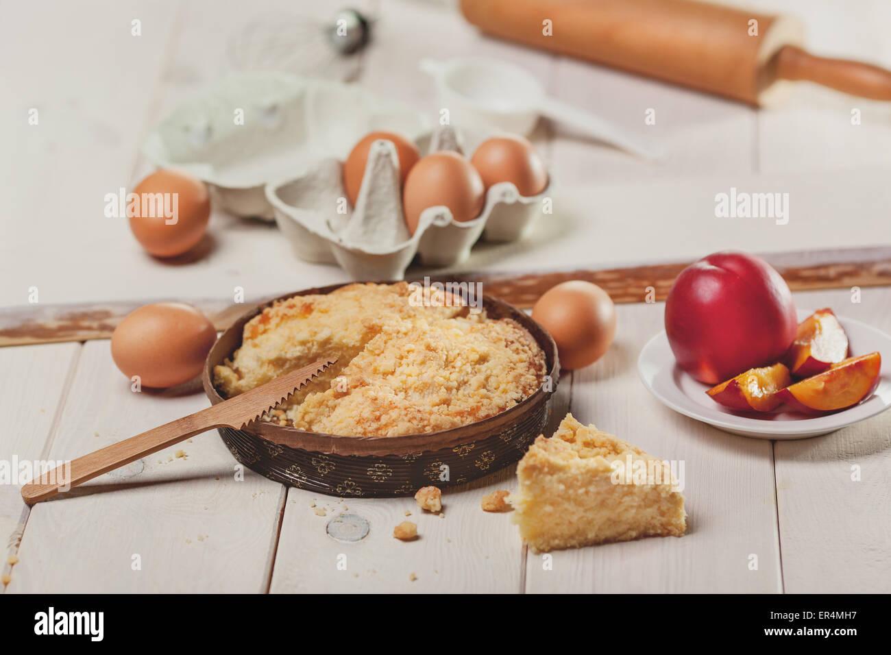 Peaches cake on white wooden planks. Debica, Poland - Stock Image