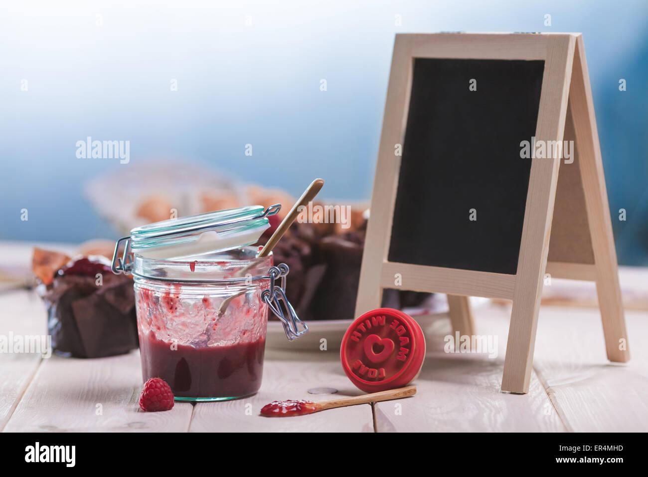 Raspberry jam on wooden planks with empty blackboard. Debica, Poland - Stock Image