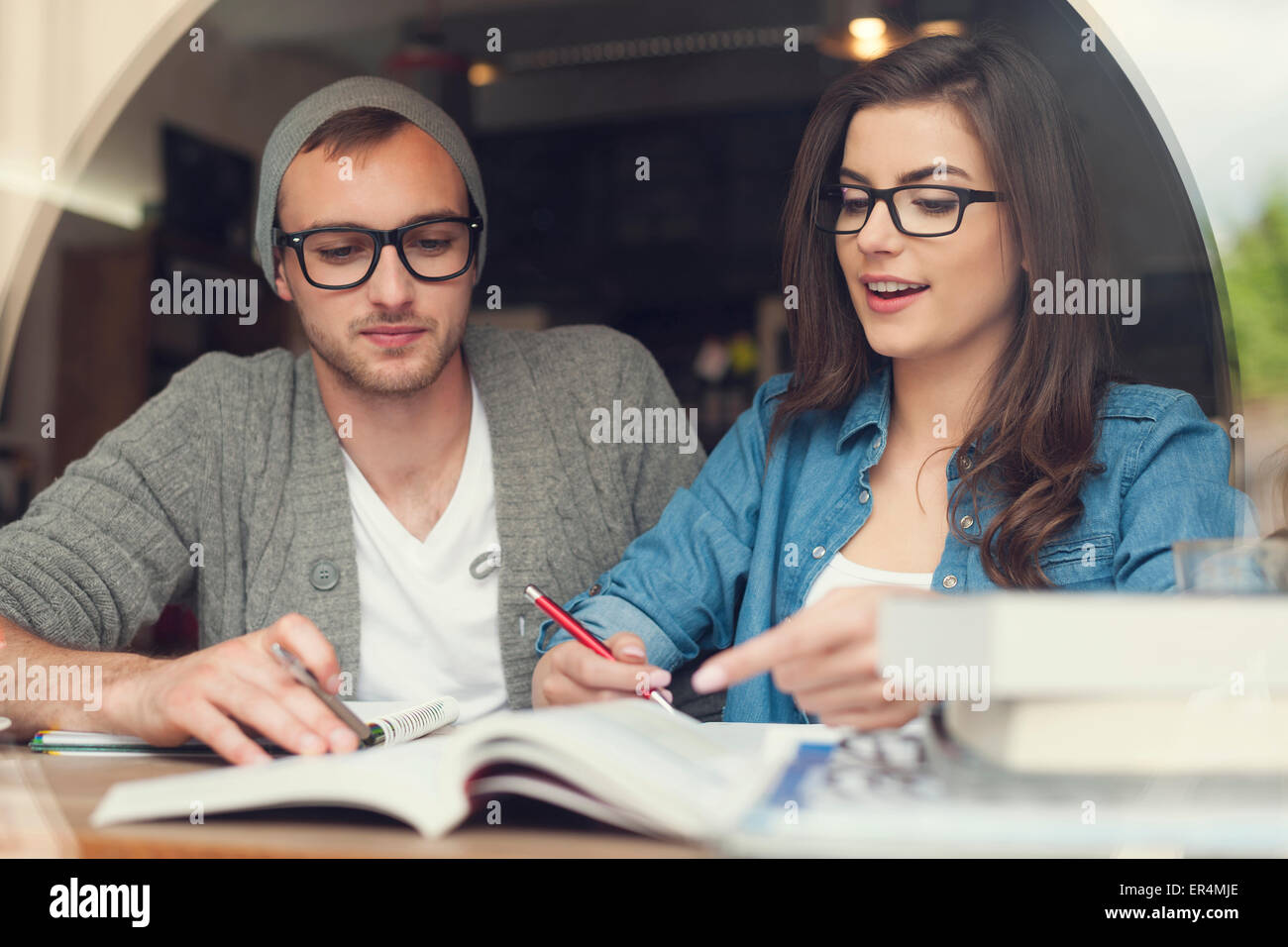 Hipster young couple studying together at cafe. Krakow, Poland - Stock Image