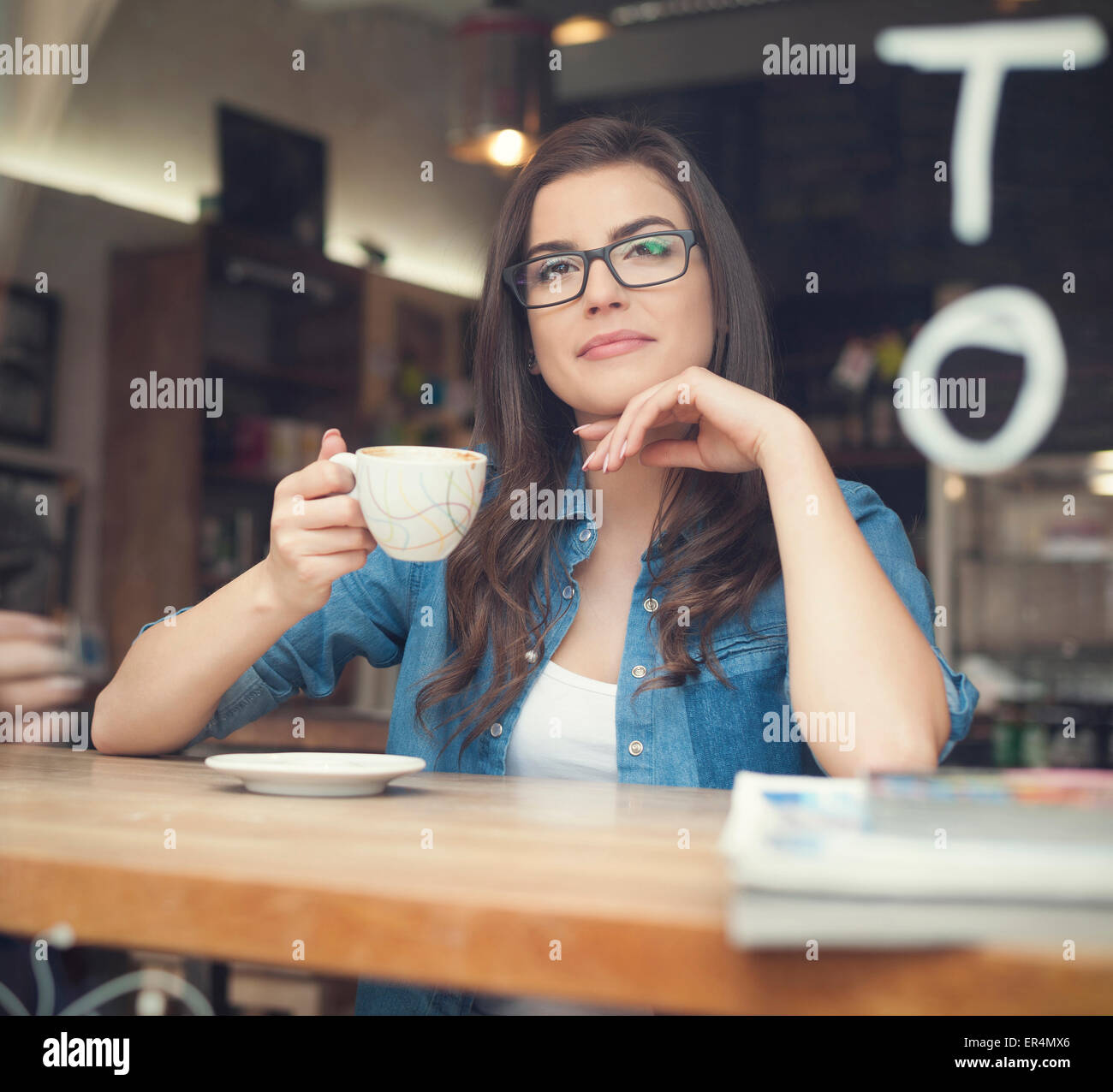 Portrait of beautiful woman drinking coffee at cafe. Krakow, Poland - Stock Image