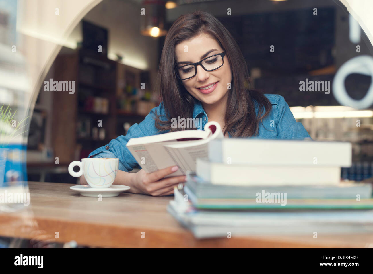 Hipster woman studying at cafe. Krakow, Poland - Stock Image