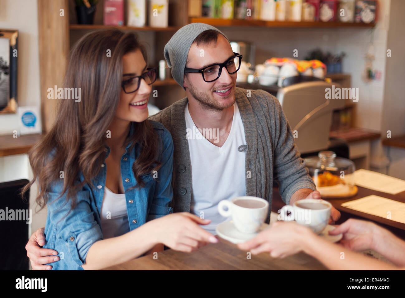 Fashion couple receiving cup of coffee from waitress. Krakow, Poland - Stock Image